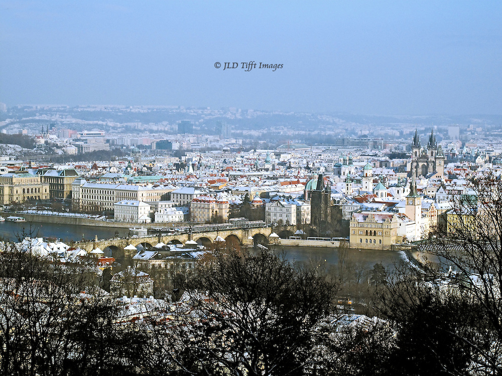 Prague cityscape from Petrin Hill toward Charles Bridge over the Vltava River; Old Town Prague beyond; in the distance, Soviet era high rise structures line the hills.