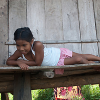 A Yanayacu Indian girl relaxes on the porch of  her family's hut in Ayacucho de Tipisha village in Peru's Amazon Jungle.