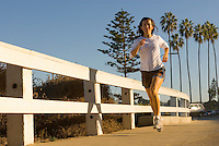 A young woman runs along the coast in La Jolla, California.