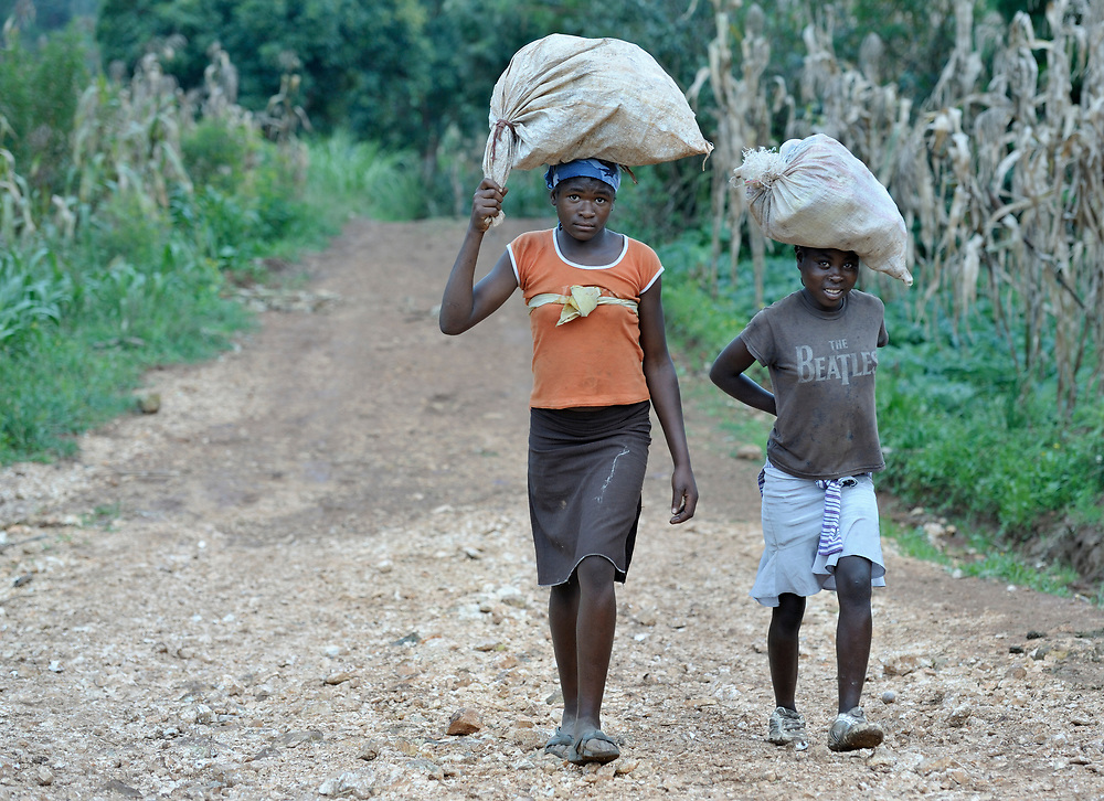 Two young women walk along a road in the mountainous community of Foret-des-Pins, Haiti.