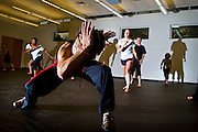 """One of the leaders of Capoeira Club, Kenji Yoshino '11 demonstrates a 'esquiva lateral' - or """"lateral escape"""" during the first part of Monday night's class in the Natatorium dance studio."""