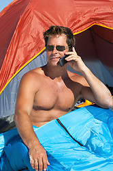 shirtless man talking on a cellphone while in a tent in White Sands, NM