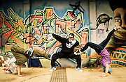 Three rappers compounding a figure near a graffiti in a wall
