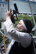A Catholic from El Salvador turns her video camera to the sky hoping for a miraculous sign from heaven at the Plaza Salvador del Mundo ( Savior of the World) as El Salvador celebrated a ceremony and mass announcing the beatification of Archbishop Oscar Romero. The Archbishop was slain at the alter of his Church of the Divine Providence by a right wing gunman in 1980. Oscar Arnulfo Romero y Galdamez became the fourth Archbishop of San Salvador, succeeding Luis Chavez, and spoke out against poverty, social injustice, assassinations and torture. Romero was assassinated while offering Mass on March 24, 1980.