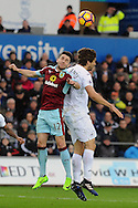 Burnley's Robbie Brady (12) challenges Swansea's Fernando Llorente for a header. Premier league match, Swansea city v Burnley at the Liberty Stadium in Swansea, South Wales on Saturday 4th March 2017.<br /> pic by  Carl Robertson, Andrew Orchard sports photography.