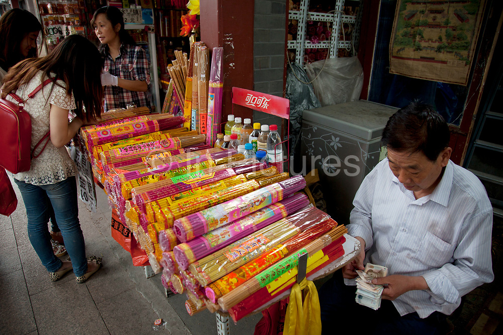 """Incense sticks for sale outside Yonghe Temple, also known as the """"Palace of Peace and Harmony Lama Temple"""", the """"Yonghe Lamasery"""", or - popularly - the """"Lama Temple"""" is a temple and monastery of the Geluk School of Tibetan Buddhism located in the northeastern part of Beijing, China. It is one of the largest and most important Tibetan Buddhist monasteries in the world. The building and the artworks of the temple is a combination of Han Chinese and Tibetan styles."""