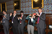 MPs, including Gavin Barwell and charity staff, use their mobile phone cameras on 28th October 2016 in London, United Kingdom. Captured in the Houses of Parliament during the Crisis Homelessness Reduction Bill. From the series Our Small World, an observation of our mobile phone obsessions
