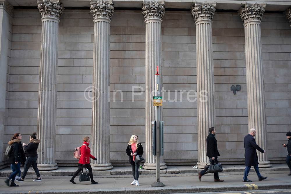 Woman waiting for a bus at the bus stop outside the Bank of England in the City of London on 5th February 2020 in London, England, United Kingdom. The City of London is a city, county and a local government district that contains the historic centre and the primary central business district CBD of London.
