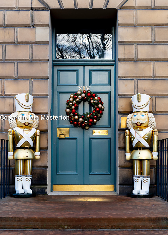 Detail of traditional Christmas wreath and large decorative statues at front door of house in New Town of Edinburgh, Scotland, UK