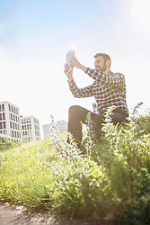 Young man taking self portrait photography with digital tablet in the park, Munich, Bavaria, Germany