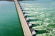 Nederland, Zeeland, Gemeente Schouwen-Duiveland, 01-04-2016; stormvloedkering Oosterschelde (Oosterscheldekering). Het is eb en het water stroomt van de Oosterschelde naar de Noordzee door het sluitgat Schaar.<br /> Eastern Scheldt storm surge barrier (Oosterscheldekering). It is low tide and the water flows from the Eastern Scheldt to the North Sea.<br /> <br /> luchtfoto (toeslag op standard tarieven);<br /> aerial photo (additional fee required);<br /> copyright foto/photo Siebe Swart