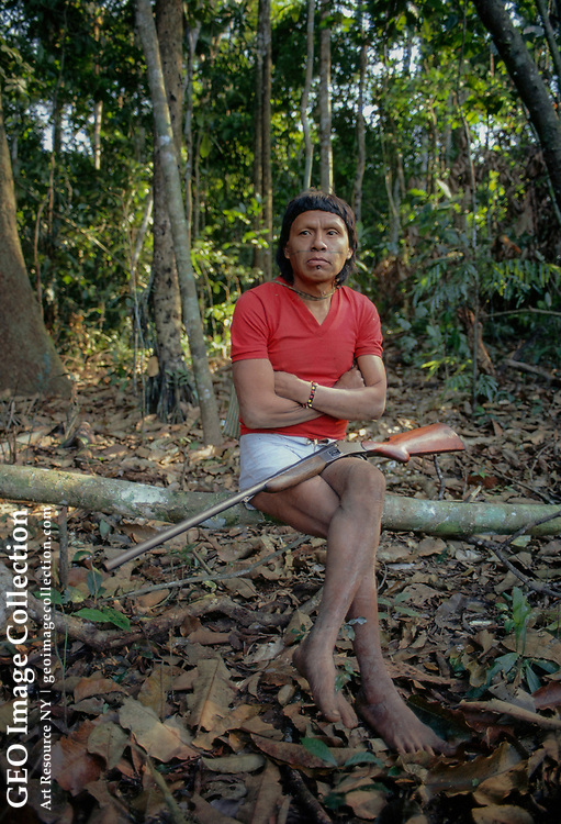 An angry Surui Indian sits in a rain forest with his rifle.