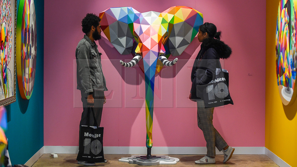 """© Licensed to London News Pictures. 04/10/2019. LONDON, UK. Visitors view """"Elefunk"""", 2019, by Okuda San Miguel at Moniker International Art Fair, an urban contemporary art fair taking celebrating its 10 year anniversary in the UK.  The fair is  place at Chelsea's Sorting Office air until 6 October 2019.  Photo credit: Stephen Chung/LNP"""