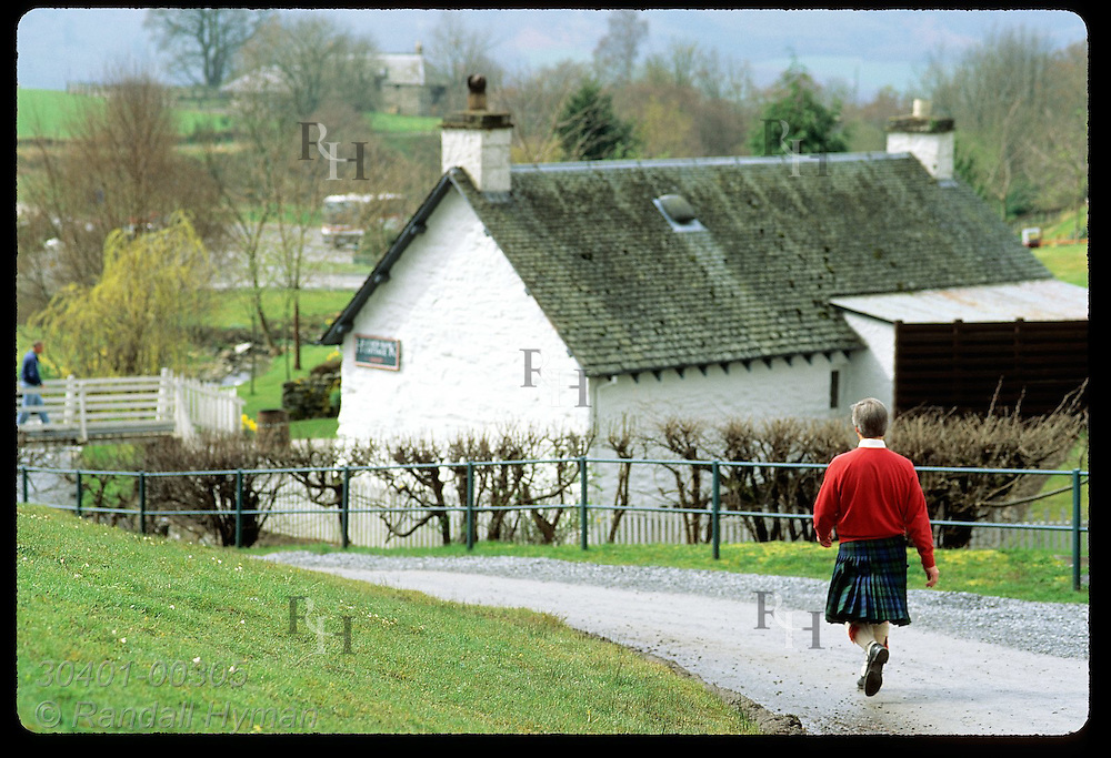 Guide in kilt walks path to gift shop at Edradour, Scotland's smallest distillery; Pitlochry. Scotland