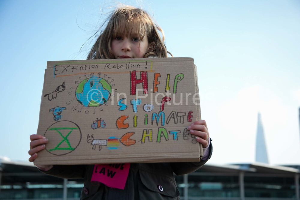 Thousands of Extinction Rebellion activists took over 5 bridges in Central London and blocked them for the day, November 17 2018, Central London, United Kingdom. Blackfriars Bridge; a peacefull occupation of the bridge begins. Freya holds up a home made placard asking for help to stop climate change. Around 11am people on all bridges sat down in the road and blocked traffic from coming through and stayed till late afternoon. The actvists believe that the government is not doing enough to avoid catastrophic climate change and they demand the government take radical action to save future generations and the planet. Many are willing to be arrested peacefully protesting and up to 80 were arrested on the day.Extinction Rebellion is a grass root climate change group started in 2018 and has gained a huge following of people commited to peaceful protests and who ready to be arrested. Their major concern is that the world is facing catastropohic climate change and they want the British government to act now to save future generations.