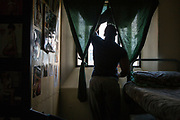 A prisoner stands at his cell window inside HMP/YOI Portland, Dorset. A resettlement prison with a capacity for 530 prisoners. Portland, Dorset, United Kingdom.