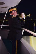Freeport, New York, USA. September 10, 2014. A bugler plays taps at night on board the boat Miss Freeport V, which sailed from the Woodcleft Canal of the Freeport Nautical Mile after a dockside remembrance ceremony in honor of victims of the terrorist attacks of September 11 2001. American Legion, Patriot Guard Riders, and Captain Frank Rizzo hosted the ceremonies on the eve of the 13th anniversary of the 9/11 attacks.