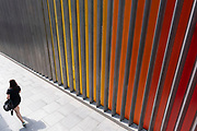 Multicoloured exterior wall which is part of an architectural design at Liverpool Street on 12th August 2020 in London, United Kingdom. Yellow, orange and red lines make up the pattern of this graphic and ordered feature of architecture which then interacts with a passer by.