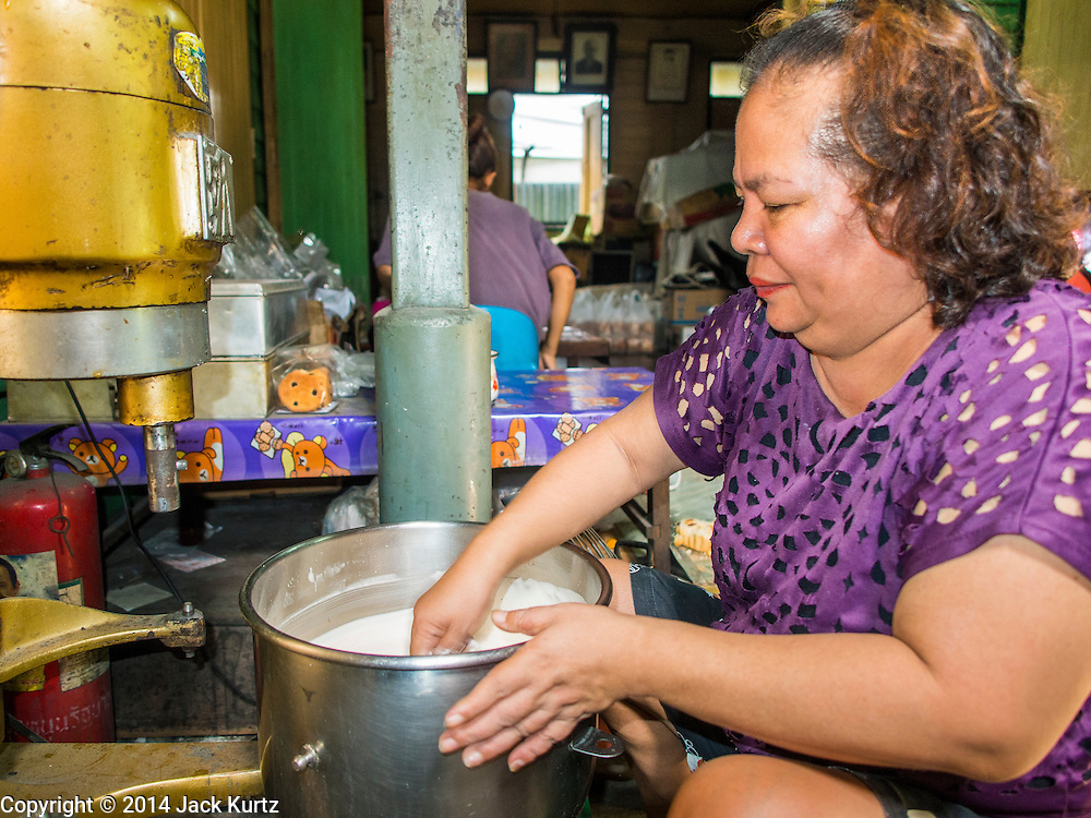"""28 OCTOBER 2014 - BANGKOK, THAILAND: A worker mixes flour, water and eggs into a batter at the Pajonglak Maneeprasit Bakery in Bangkok. The cakes are called """"Kanom Farang Kudeejeen"""" or """"Chinese Monk Candy."""" The tradition of baking the cakes, about the size of a cupcake or muffin, started in Siam (now Thailand) in the 17th century AD when Portuguese Catholic priests accompanied Portuguese soldiers who assisted the Siamese in their wars with Burma. Several hundred Siamese (Thai) Buddhists converted to Catholicism and started baking the cakes. When the Siamese Empire in Ayutthaya was sacked by the Burmese the Portuguese and Thai Catholics fled to Thonburi, in what is now Bangkok. The Portuguese established a Catholic church near the new Siamese capital. Now just three families bake the cakes, using a recipe that is 400 years old and contains eggs, wheat flour, sugar, water and raisins. The same family has been baking the cakes at the Pajonglak Maneeprasit Bakery, near Santa Cruz Church, for more than 245 years. There are still a large number of Thai Catholics living in the neighborhood around the church.   PHOTO BY JACK KURTZ"""