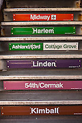 """Station signs marking the transit lines on the stairs of the """"L"""", the elevated rapid transit system in Chicago, IL, USA."""