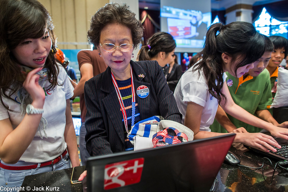 07 NOVEMBER 2012 - BANGKOK, THAILAND: Thai educators at the Google booth monitor US election results at an election watch party sponsored by the US Embassy in Bangkok. Google has a booth at the party that used Google products to display real time results. US President Barack Obama won a second term Tuesday when he defeated Republican Mitt Romney. Preliminary tallies gave the President more than 300 electoral votes, well over the 270 needed to win. The election in the United States was closely watched in Thailand, which historically has very close ties with the United States. The American Embassy in Bangkok sponsored an election watching event which drew thousands to a downtown Bangkok hotel. American Democrats in Bangkok had their own election watch party at a restaurant in Bangkok.      PHOTO BY JACK KURTZ