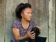 Yai wearing a hairpiece made from her own hair collected from her hairbrush over many years in the Hmong village of Ban Pom Khor, Houaphan province, Lao PDR