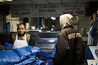 Workers begin the process of opening the fish market for business on a snowy winter's morning in The Italian Market, Philadelphia, PA.