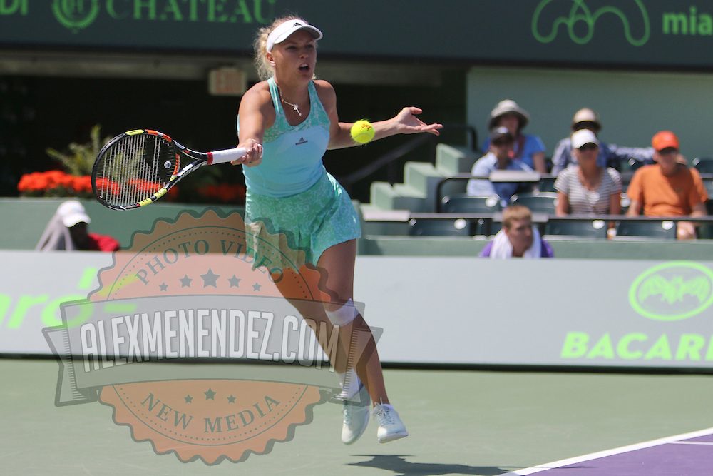 Caroline Wozniacki of Denmark returns a shot from Venus Williams of the United States during their match at the Miami Open tennis tournament at Crandon Park on Monday, March 30, 2015 in Key Biscayne, Florida. Williams won the match.  (AP Photo/Alex Menendez)