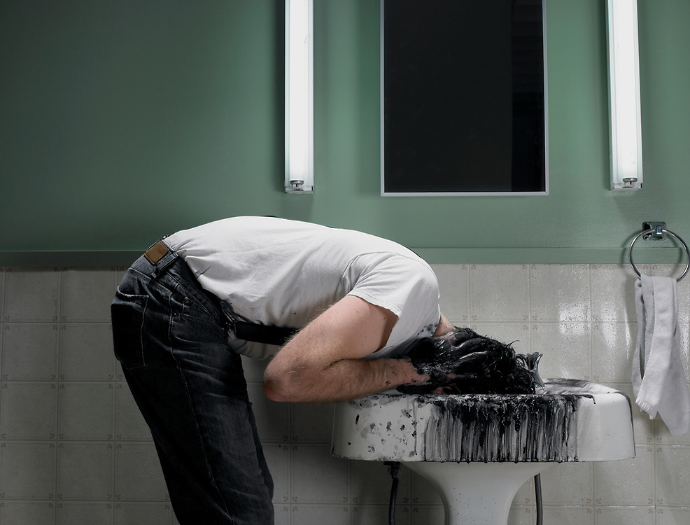 30 something man with head in sink covered in black paint