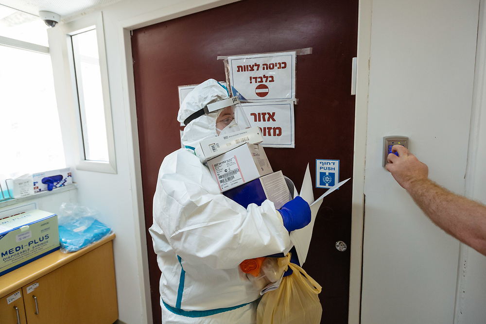 A nurse carries medical supplies as she enters an isolated ward to treat Covid-19 Novel Coronavirus patients, at the Hadassah Ein Kerem Hospital, in Jerusalem, Israel, on April 20, 2020.