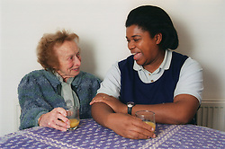 Carer sitting at table with elderly woman laughing,