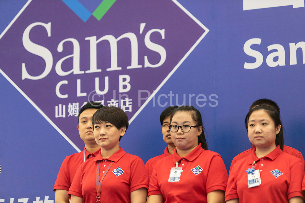 Employees stand in a line during the ribbon cutting ceremony of a Wal-Mart Stores Inc. owned and operated Sams Club store during its opening day in Tianjin, China, on Wednesday, Sept. 28, 2016.