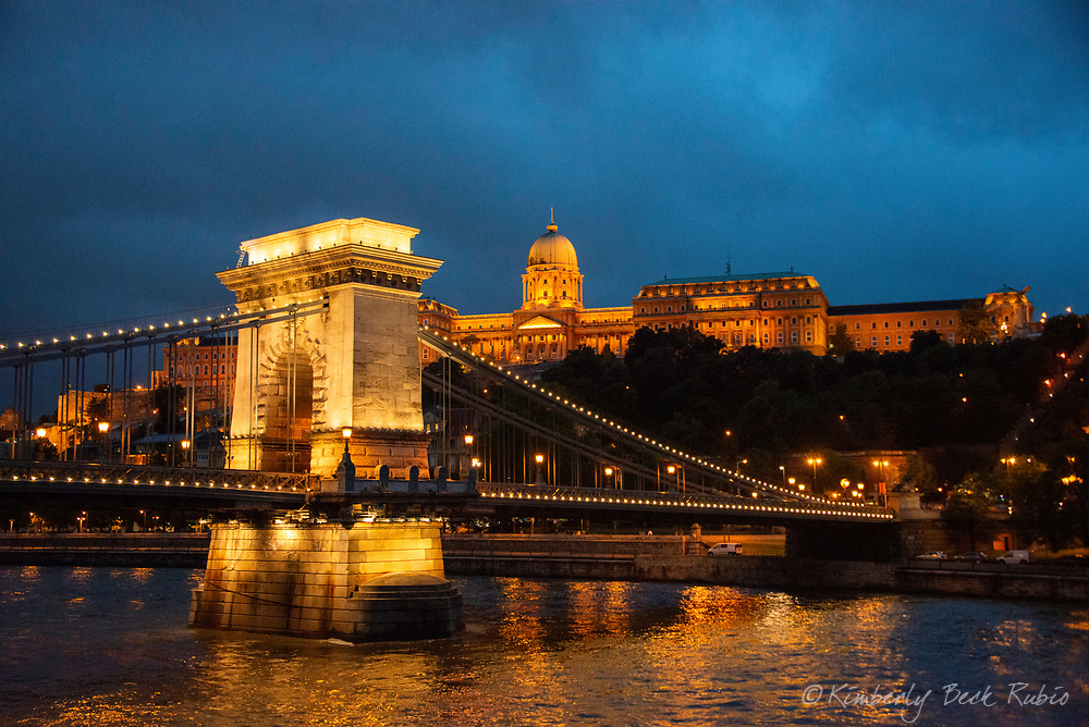 Széchenyi Chain Bridge with Buda Castle in the background from a evening cruise on the Danube River in Budapest, Hungary.