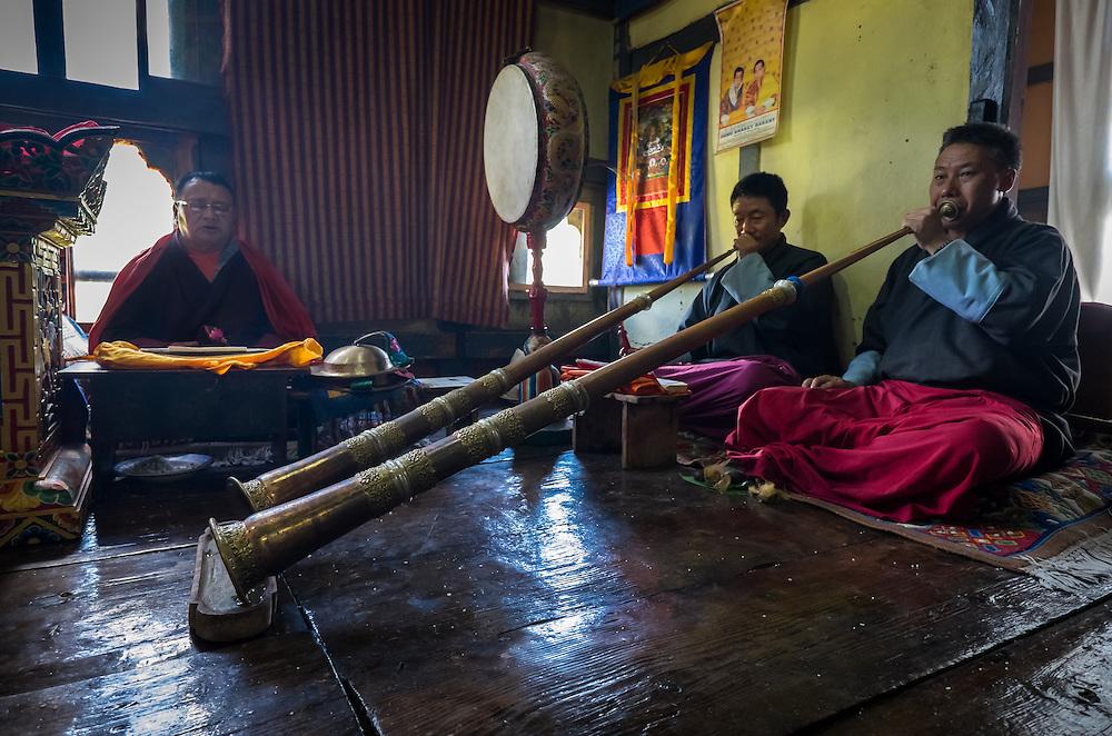PARO, BHUTAN - CIRCA OCTOBER 2014: Bhutanese men chanting and playing Tibetan trumpets during a ritual in Paro, Bhutan