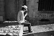 A man smoking in the summer sun in Uzès, a historic town in the Gard department in the south of France.