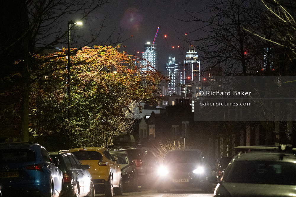 The glow of distant buildings overlooks the bright headlights of a passing car and other parked vehicles in a dark residential street in Herne Hill, south London on 21st January 2021, in London, England.