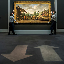 """© Licensed to London News Pictures. 07/12/2020. LONDON, UK. Social distancing arrows on the carpet and technicians presenting """"The Wine Harvest"""" by David Teniers The Younger (Est. £3-5m). Preview of Sotheby's upcoming Christmas Sale Series of Old Masters and Treasures - paintings and objects spanning 800 Years.  The sales will be at Sotheby's New Bond Street gallery.  Photo credit: Stephen Chung/LNP"""