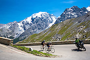 Cyclists ride roadbikes behind motorcycle uphill on The Stelvio Pass, Passo dello Stelvio, Stilfser Joch, in the Alps, Italy
