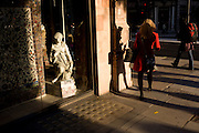 Woman drops item in front of small girl statue credited to the 19th century Florence-born artist Raffaello Romanelli.  Part of a sequence of 4 images showing the woman in red dropping the Oyster card and subsequently bending down and picking it up.