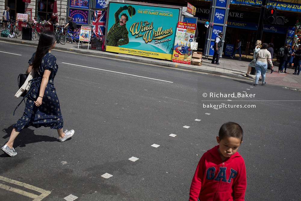 Pedestrians cross the road opposite a Wind in the Willows ad, on 31st July 2017, in Tottenham Court Road, London, England.
