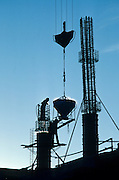 Alaska. Anchorage. Steel workers help a crane with bucket of concrete for construction of a highrise building.