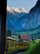 """At sunset, see Lauterbrunnen Breithorn (3780 meters or 12,402 feet elevation) from Wengernalpbahn cog train in Lauterbrunnen Valley, Berner Oberland, Switzerland, the Alps, Europe. The world's longest continuous rack and pinion railway (Wengernalpbahn) goes from Grindelwald up to Kleine Scheidegg and down to Wengen and Lauterbrunnen. The Bernese Highlands are the upper part of Bern Canton. IUNESCO lists """"Swiss Alps Jungfrau-Aletsch"""" as a World Heritage Area (2001, 2007)."""