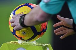 The referee picks up the match ball