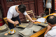 A man writes a prayer on a temple tile at Chenghuang Miao or City God Temple in Yu Yuan Gardens bazaar Shanghai, China