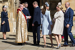 Windsor, UK. 21st April 2019. The Duke of Cambridge, followed by the Duchess of Cambridge and Mike and Zara Tindall, shakes the hand of the Dean of Windsor, the Rt Revd David Conner KCVO, as he arrives to attend the Easter Sunday service at St George's Chapel in Windsor Castle.