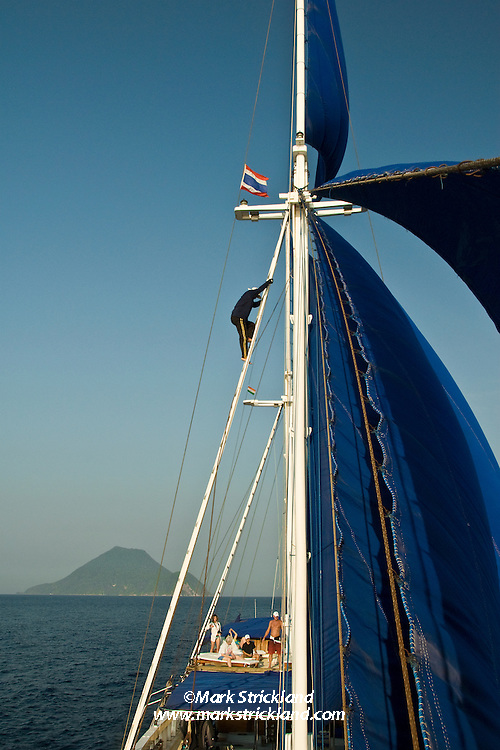 A crewmember descends after setting the forward topsail aboard s/y Siren. The disitinctive profile of Narcondam Island, seen in the distance, is unmistakenly volcanic. Narcondam Island, Andaman Islands, India, Andaman Sea