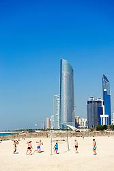 Volleyball game on Corniche beach with skyline in Abu Dhabi United Arab emirates