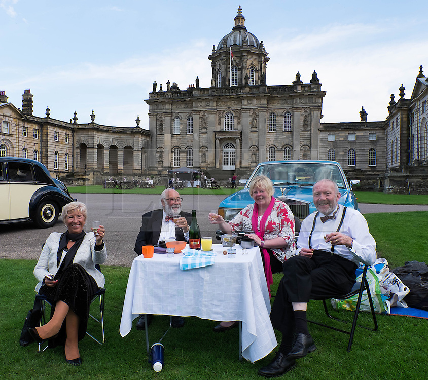 © Licensed to London News Pictures.22/08/15<br /> Castle Howard, North Yorkshire, UK. <br /> <br /> A group of friends sit in front of their car enjoying a drink and a picnic as hundreds of people attend the 25th anniversary of the Castle Howard Proms event near York. The theme of the event this year is a commemoration of the 75th anniversary of the Battle of Britain and the 70th anniversary of VE day and brings an evening of classic musical favourites celebrating Britishness to the lawns of Castle Howard.<br /> <br /> Photo credit : Ian Forsyth/LNP