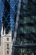 The Swiss re tower top left, aka The Gherkin and the church of St. Mary Axe in the City of London, the capitals historic financial district, on 2nd August 2018, in London, England.