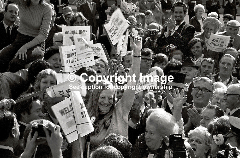 Merseyside-born, Belfast by adoption, Mary Peters, holds aloft the Gold Medal she won in the pentathlon at the Munich Olympics, as she arrives at Belfast City Hall for a civic reception. 197209080534j.<br /> <br /> Copyright Image from Victor Patterson, Belfast, UK<br /> <br /> t: +44 28 9066 1296 (from Rep of Ireland 048 9066 1296)<br /> m: +44 7802 353836<br /> e: victorpattersonbelfast@gmail.com<br /> <br /> www.images4media.com<br /> <br /> Please see my full Terms and Conditions of Use at https://www.images4media.com/p/terms-conditions - it is IMPORTANT that you familiarise yourself with them.<br /> <br /> Images used online incur an additional cost. This cost should be agreed in writing in advance. Online images must be visibly watermarked i.e. © Victor Patterson or that of the named photographer within the body of the image. The original metadata must not be deleted from images used online.<br /> <br /> This image is only available for the use of the download recipient i.e. television station, newspaper, magazine, book publisher, etc, and must not be passed on to a third party. It is also downloaded on condition that each and every usage is notified within 7 days to victorpattersonbelfast@gmail.com.<br /> <br /> The right of Victor Patterson (or the named photographer) to be identified as the author is asserted in accordance with The Copyright Designs And Patents Act (1988). All moral rights are asserted.
